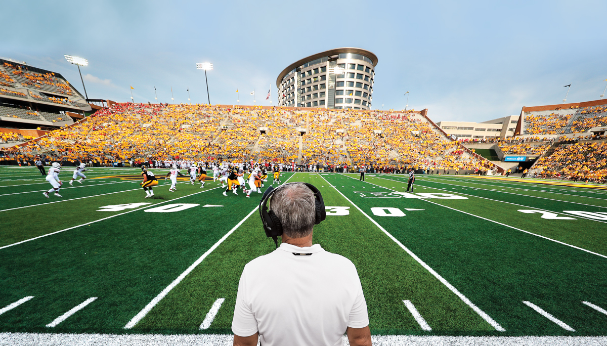 the Iowa Hawkeyes play a football game at Kinnick Stadium; UI Stead Family Children's Hospital is seen overlooking the stadium in the background