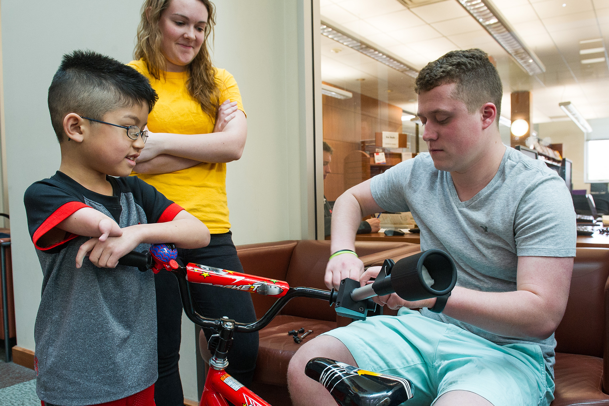 university of iowa engineering students work on device that allows a young boy to ride his bike