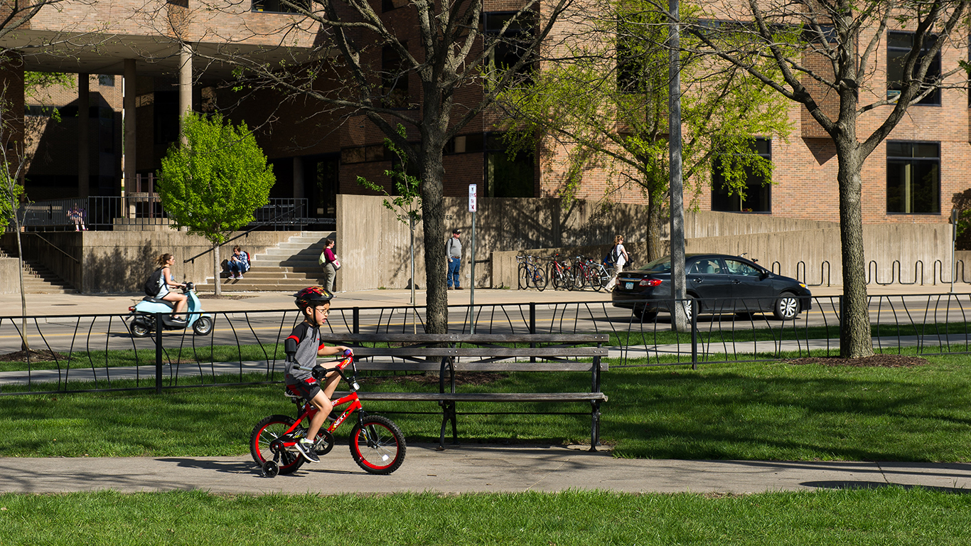 Jonny Cole smiles as he tests out the assistive device that allows him to better ride a bicycle. Alicia Truka, one of the four biomedical engineering students who designed the device, follows Jonny as he rides