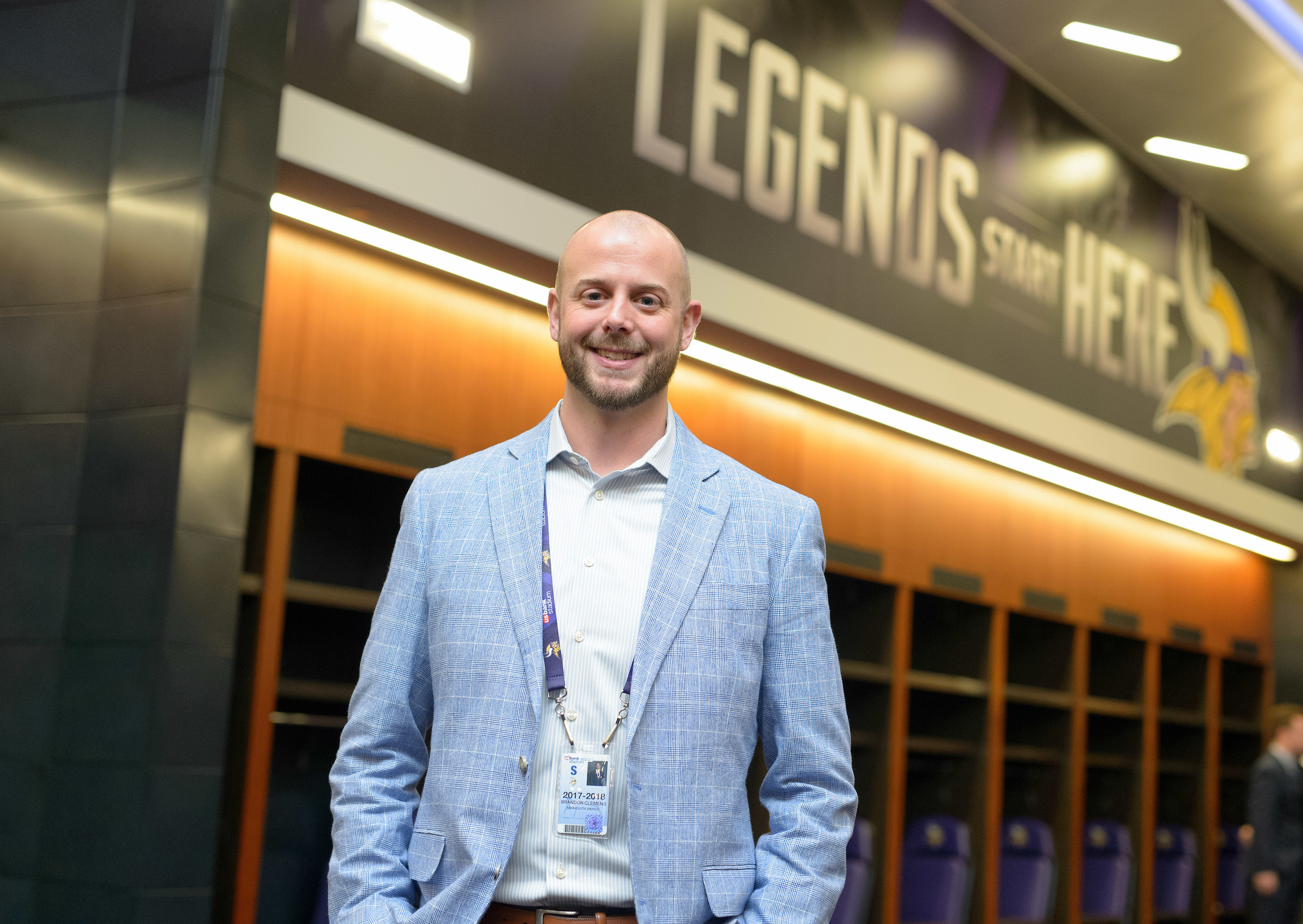 University of Iowa graduate Brandon Clemens stands inside a facility of the Minnesota Vikings, the words Legends Start Here are written on the wall behind him