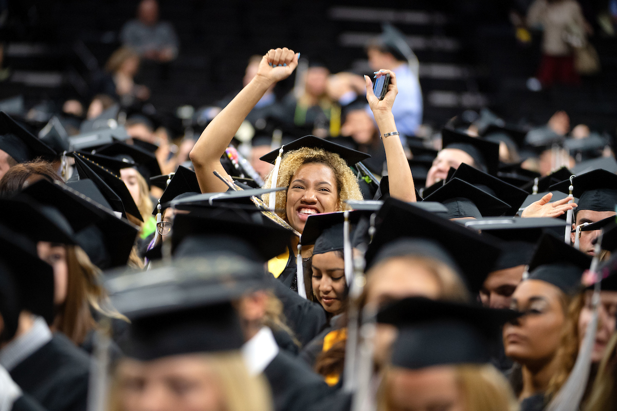 University of Iowa students gather at commencement; one student can be seen raising her arms in celebration