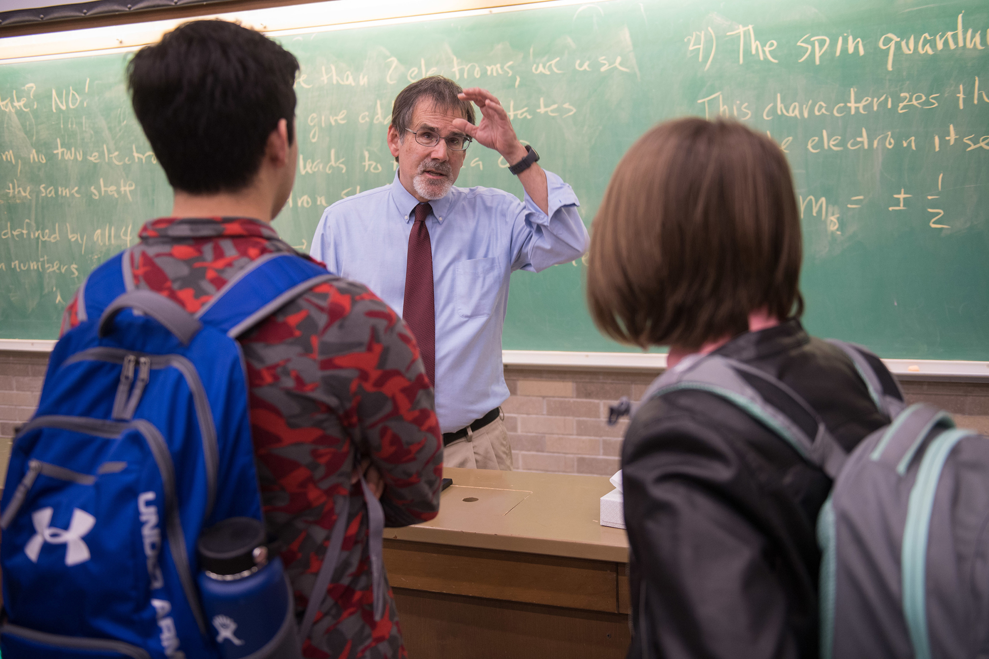 university of iowa professor craig kletzing conversing with two of his students in a classroom