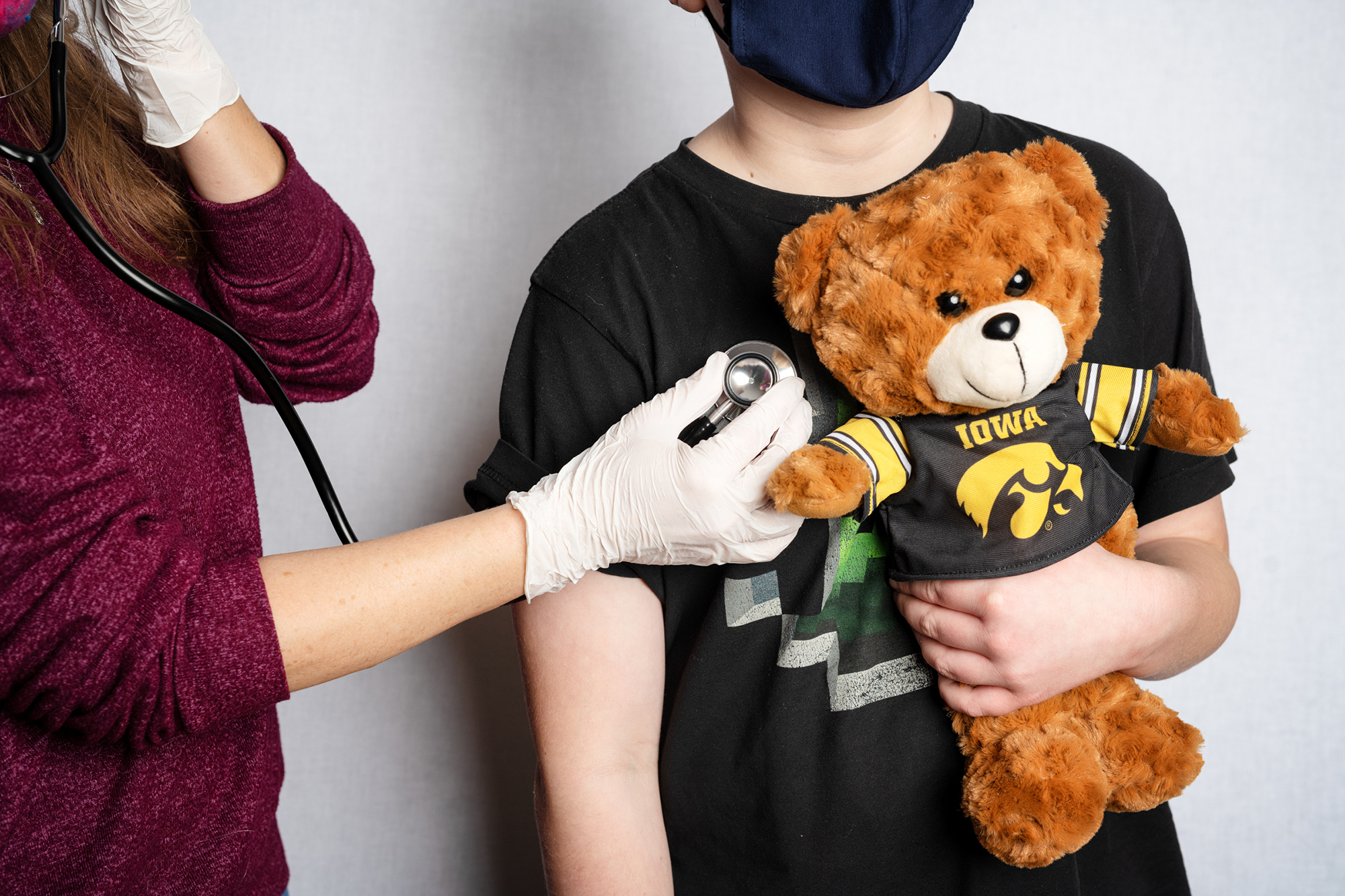 A child is examined while holding a teddy bear