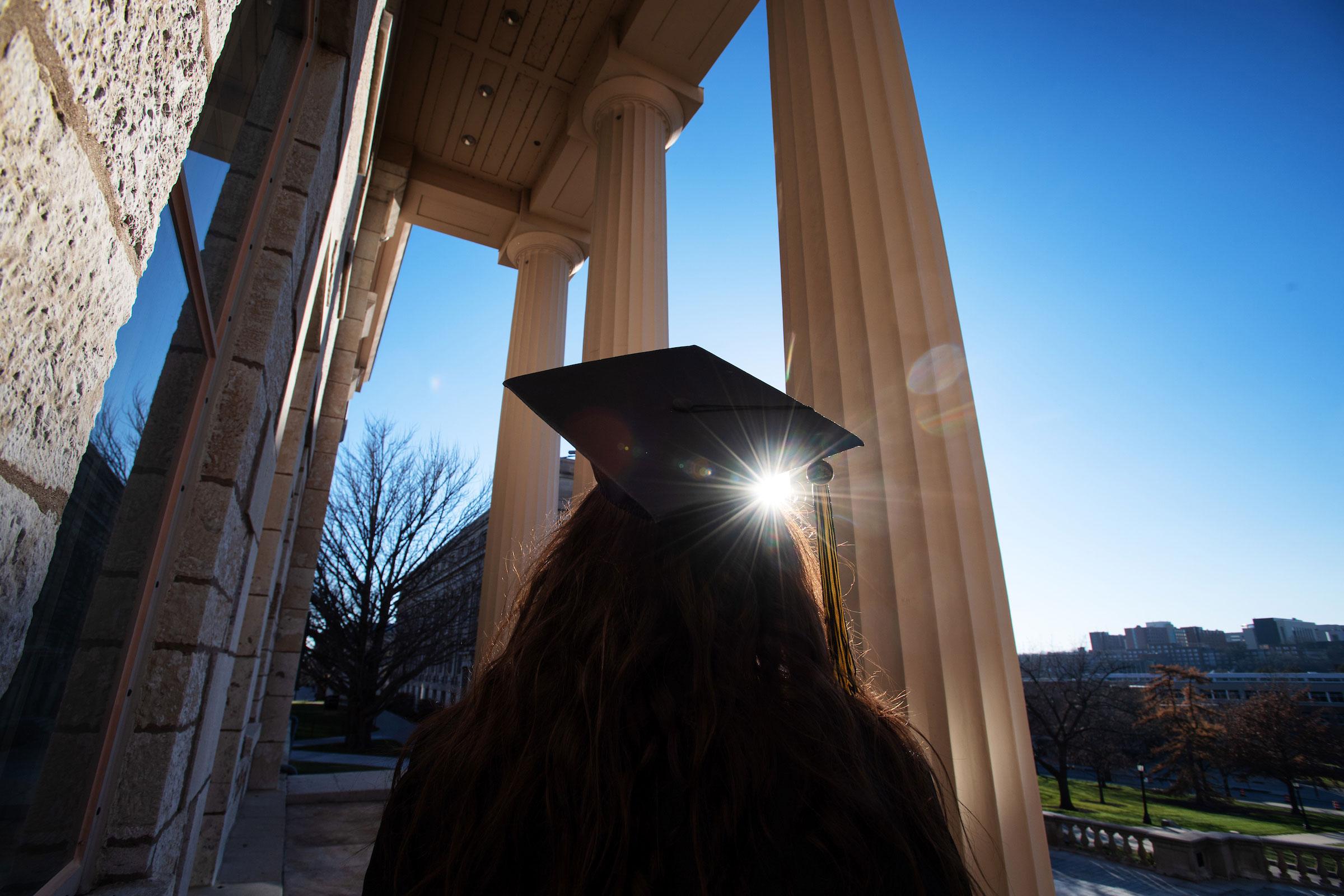 Graduate looking up toward Old Capital pillars