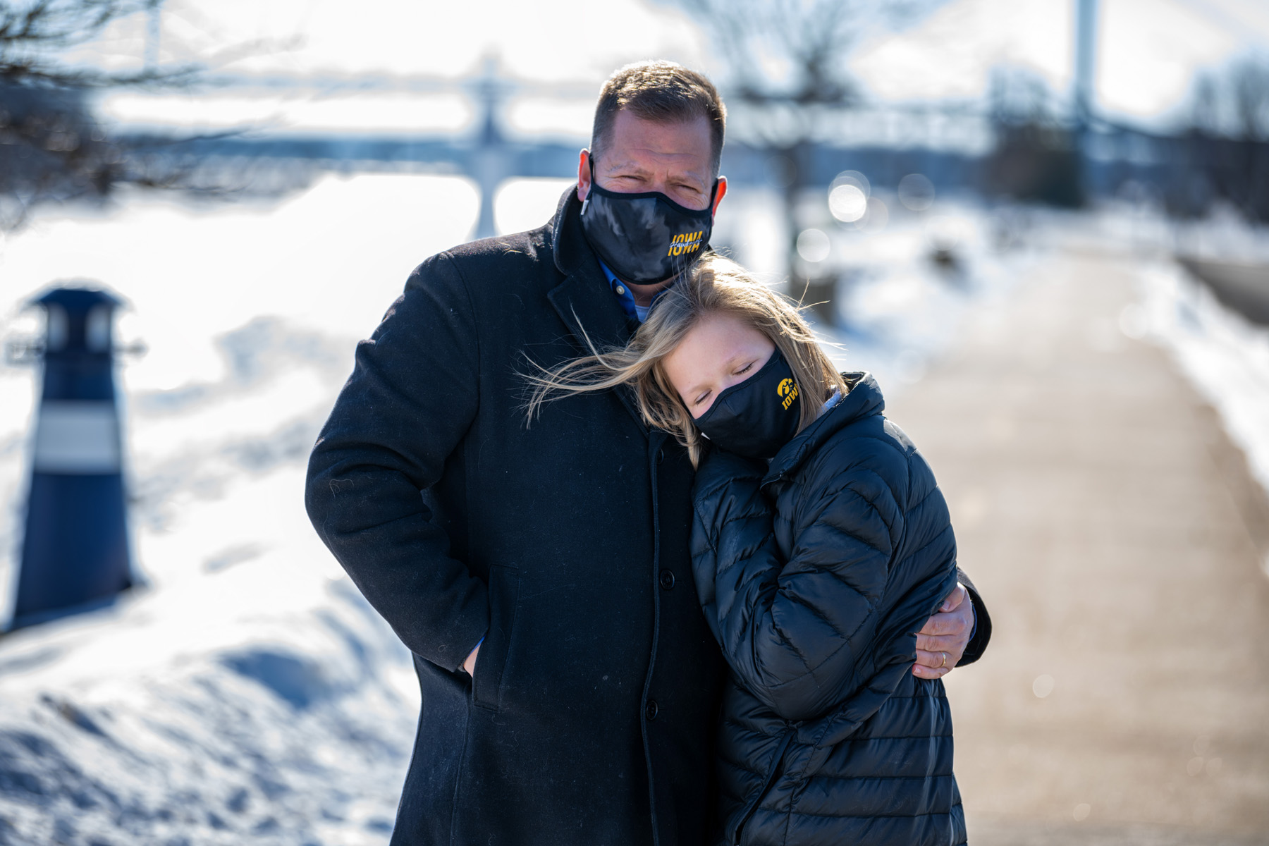 Daniel Ivory and his daughter Lydia wearing face masks with Tiger hawk logos, standing outdoors on a sunny winter day