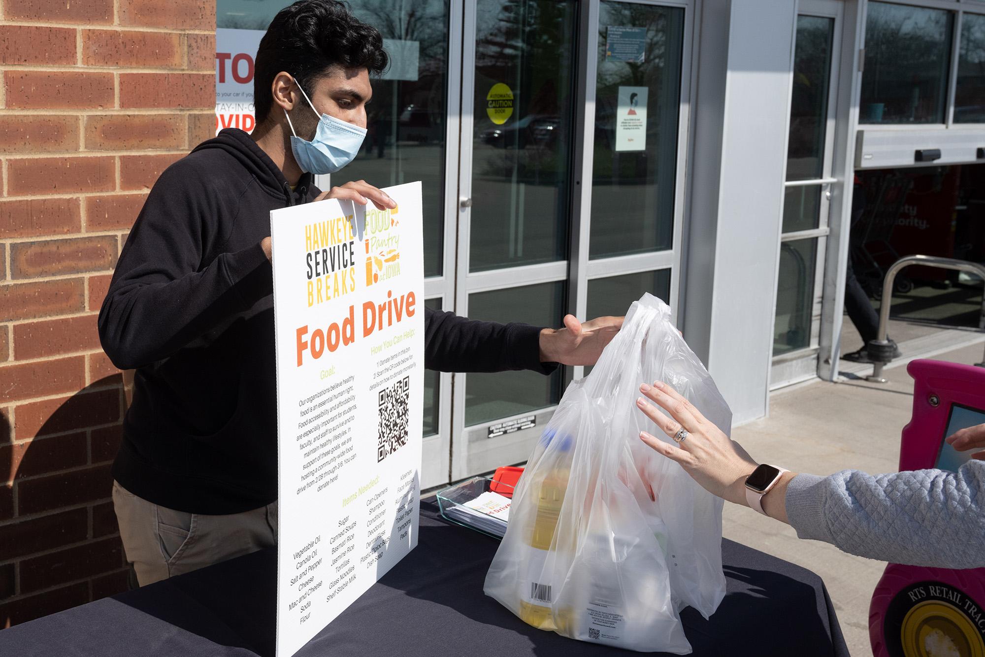 Prateek Raikwar, a third-year neuroscience and music major from Iowa City, works at a food drive for Hawkeye Service Breaks