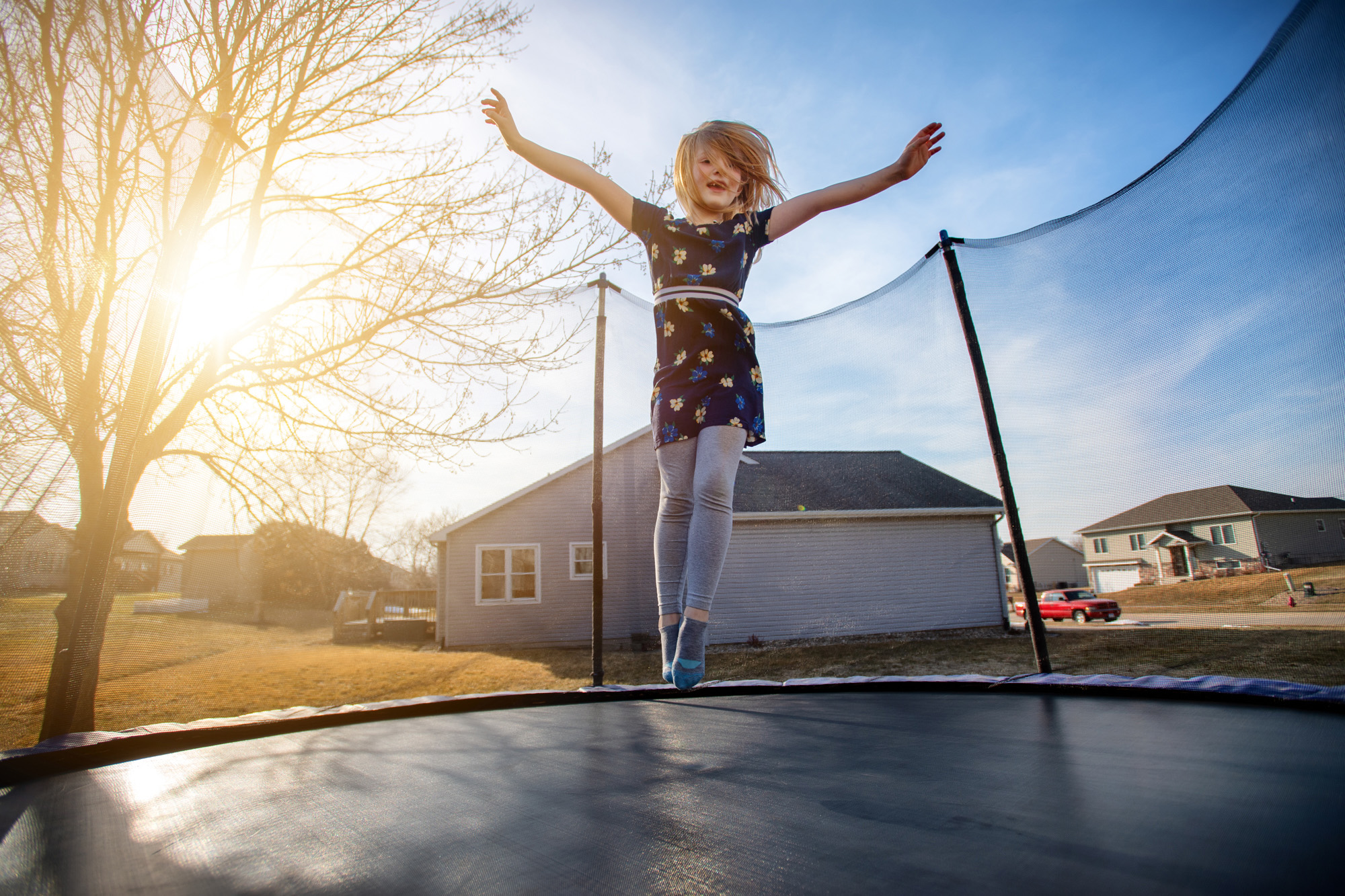 young girl jumping on a trampoline as the sun begins to set