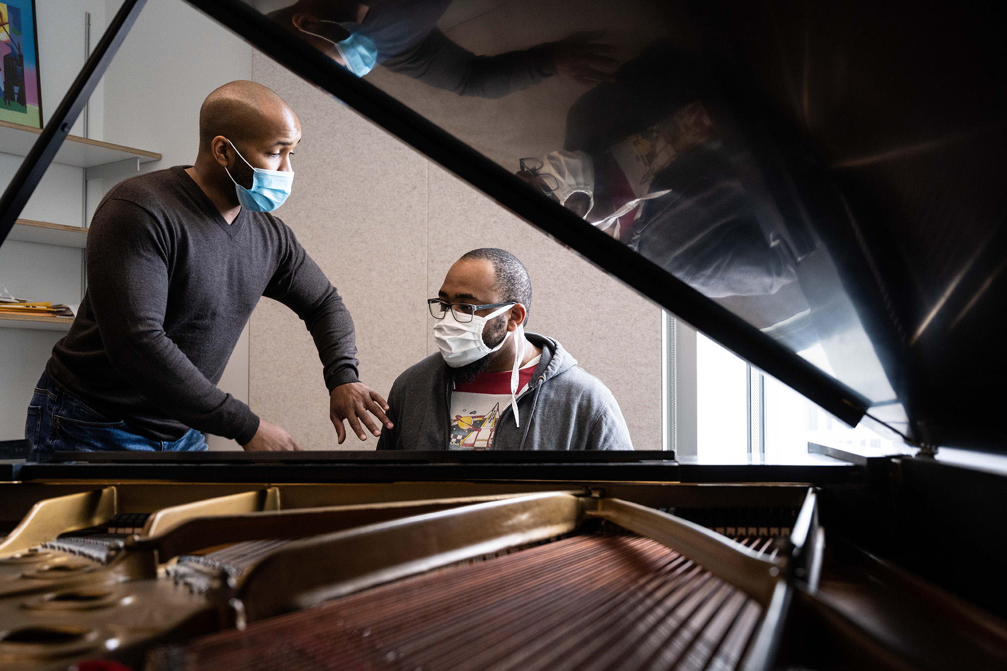 University of Iowa jazz studies faculty member William Menefield works with a student at a piano