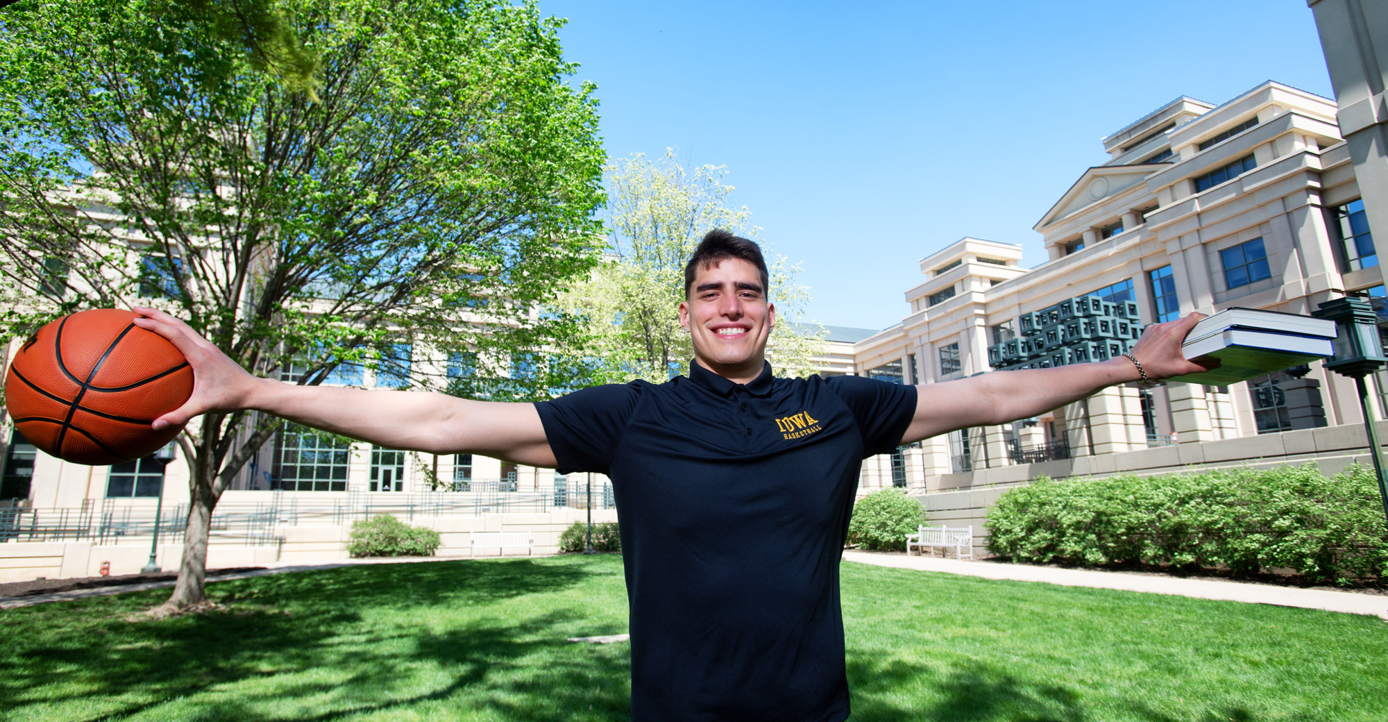 Luka Garza on the University of Iowa campus, holding textbooks and a basketball