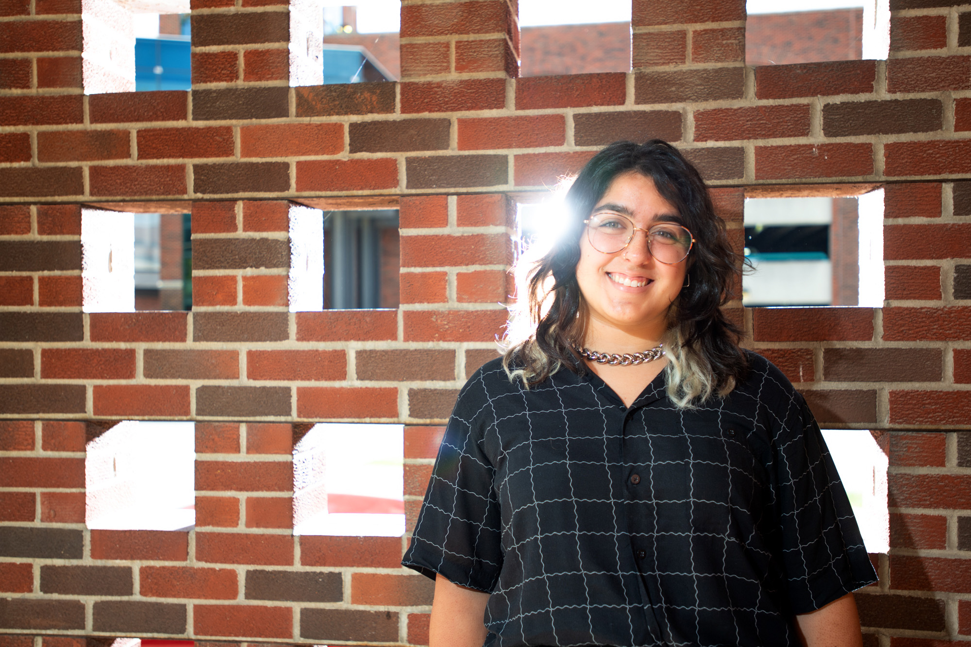University of Iowa graduate student Bianca Robles-Munoz standing near a brick wall with sunlight coming through openings