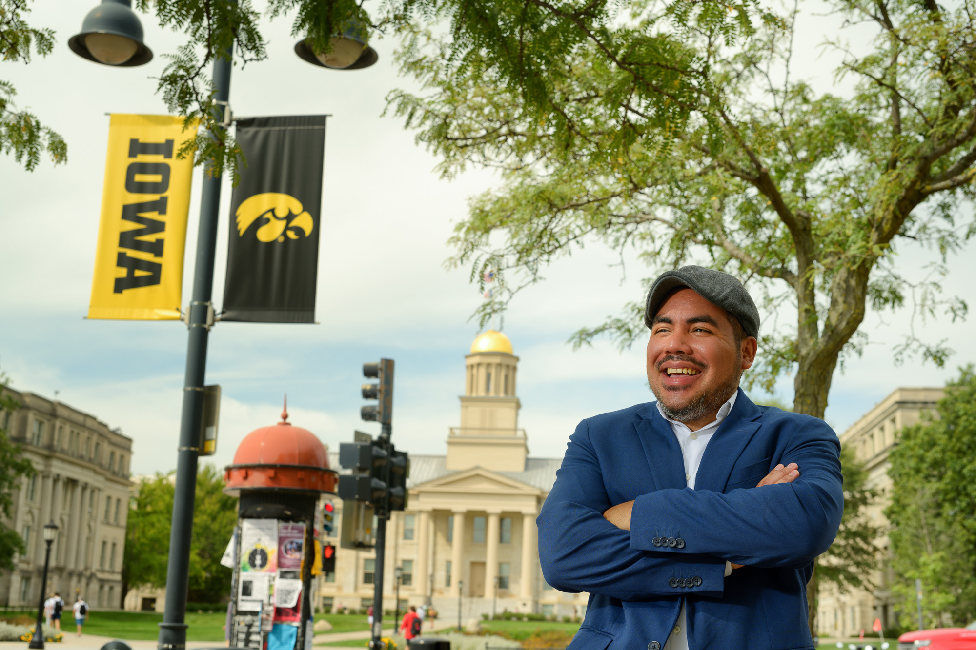University of Iowa lecturer Jorge Guerra standing on the university of iowa campus; Iowa and tiger hawk banners and the old capitol are visible in the background