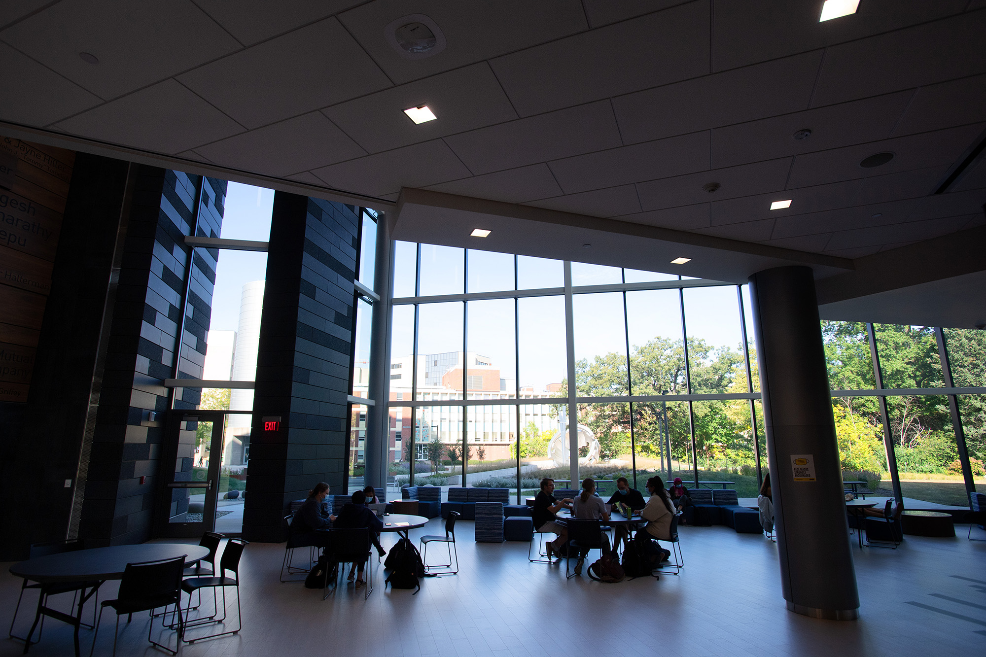interior shot from the University of Iowa College of Pharmacy Building. People sit throughout the room; a large wall of windows shows buildings outside