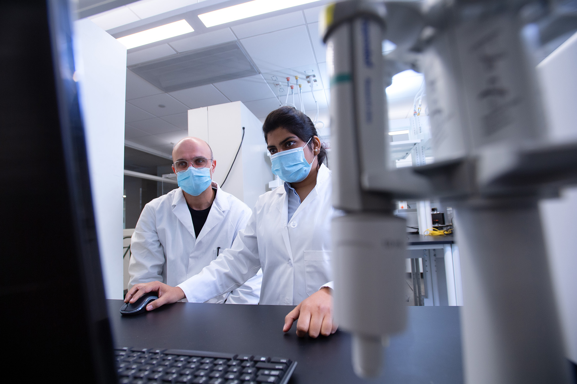 a faculty member and a student working in a lab in the University of Iowa College of Pharmacy Building