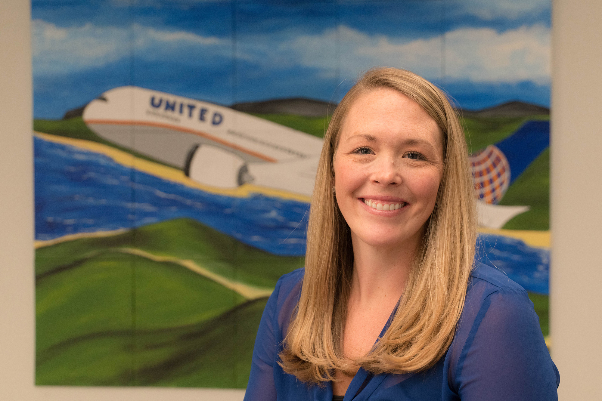 Michelle McCarthy, University of Iowa alumna, posing for a portrait in front of a United Airlines mural