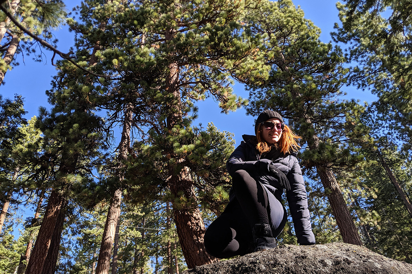 university of iowa alum lauryn ash on a boulder in a forest