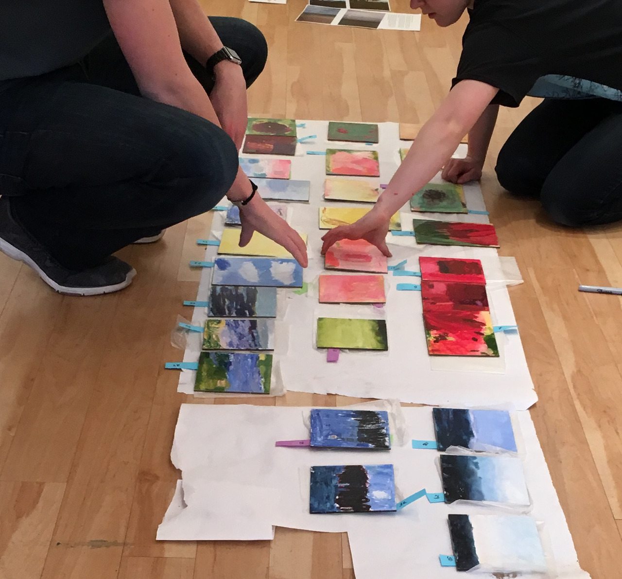 students arranging artwork on paper