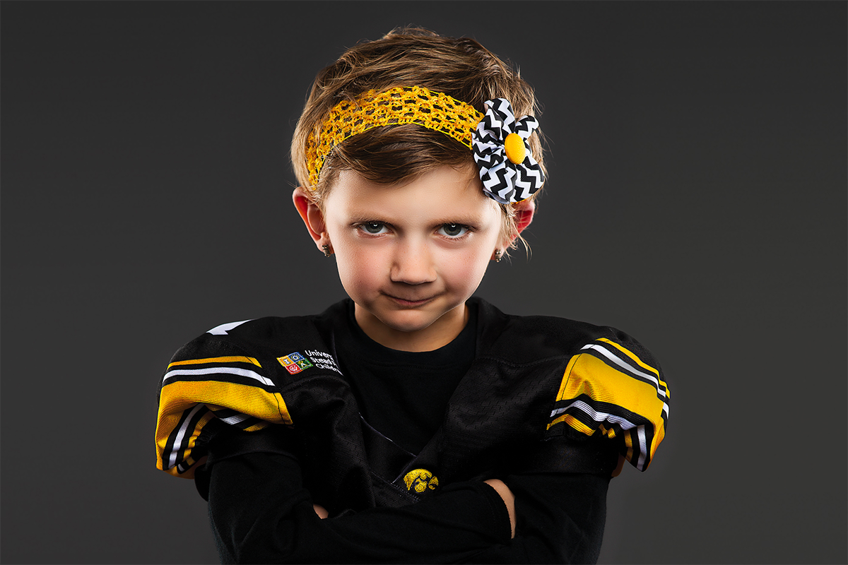 university of iowa stead family children's hospital patient and kid captain harper stribe posing in hawkeye jersey