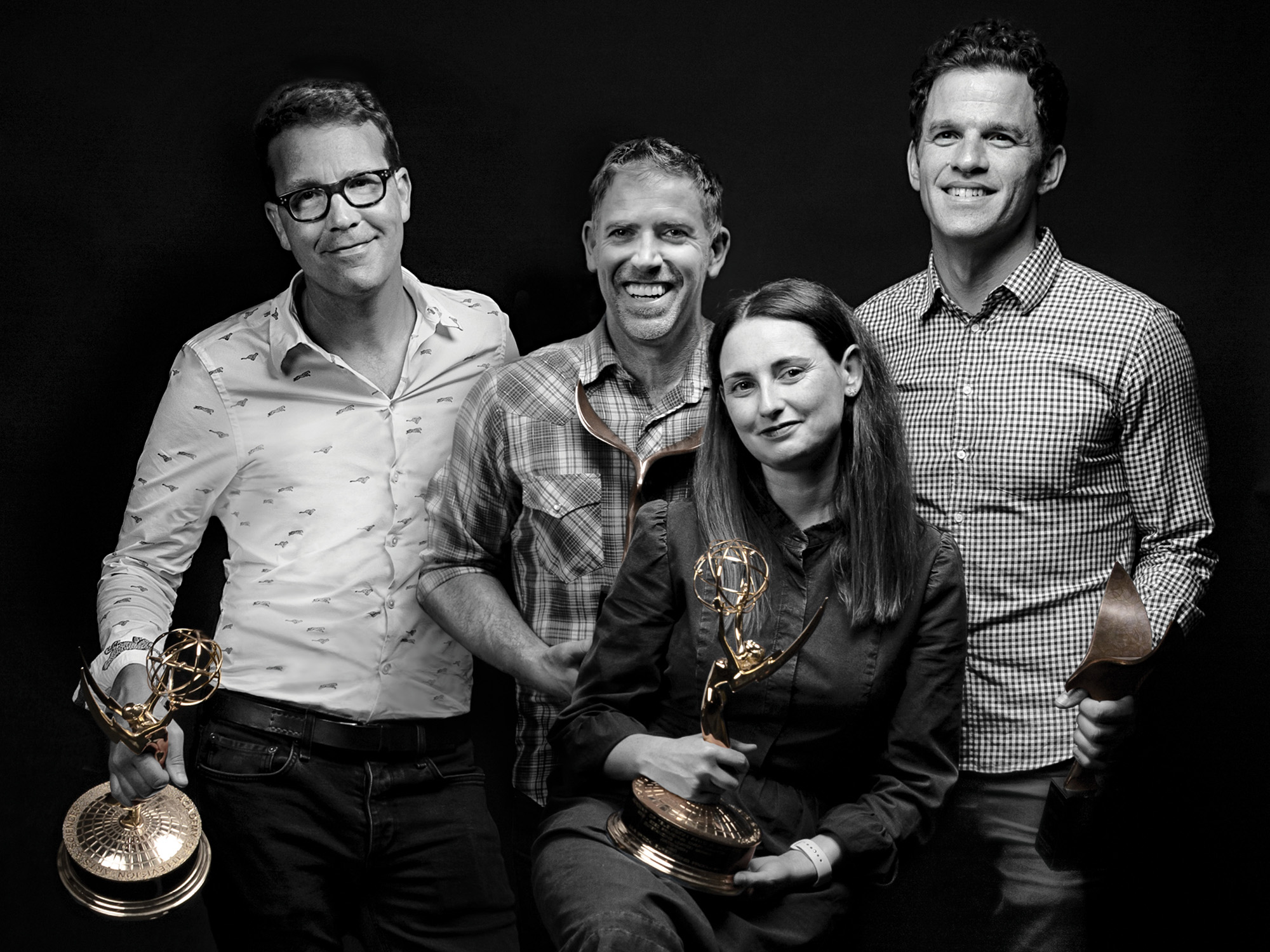 the four writers of Castle Rock pose together for a photo, two of them holding award statues