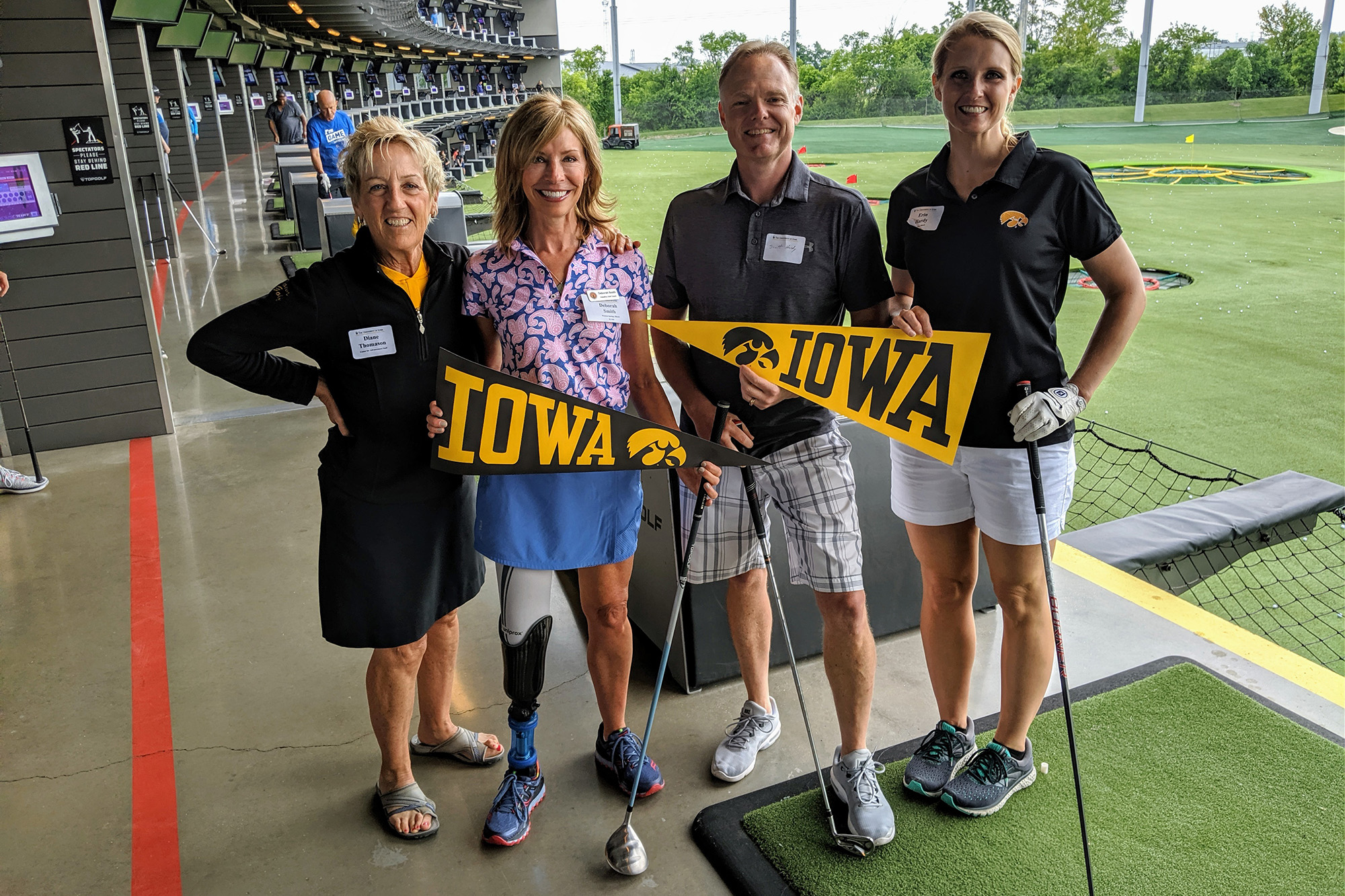 University of Iowa alumna Deborah Smith stands with three friends at a golf facility