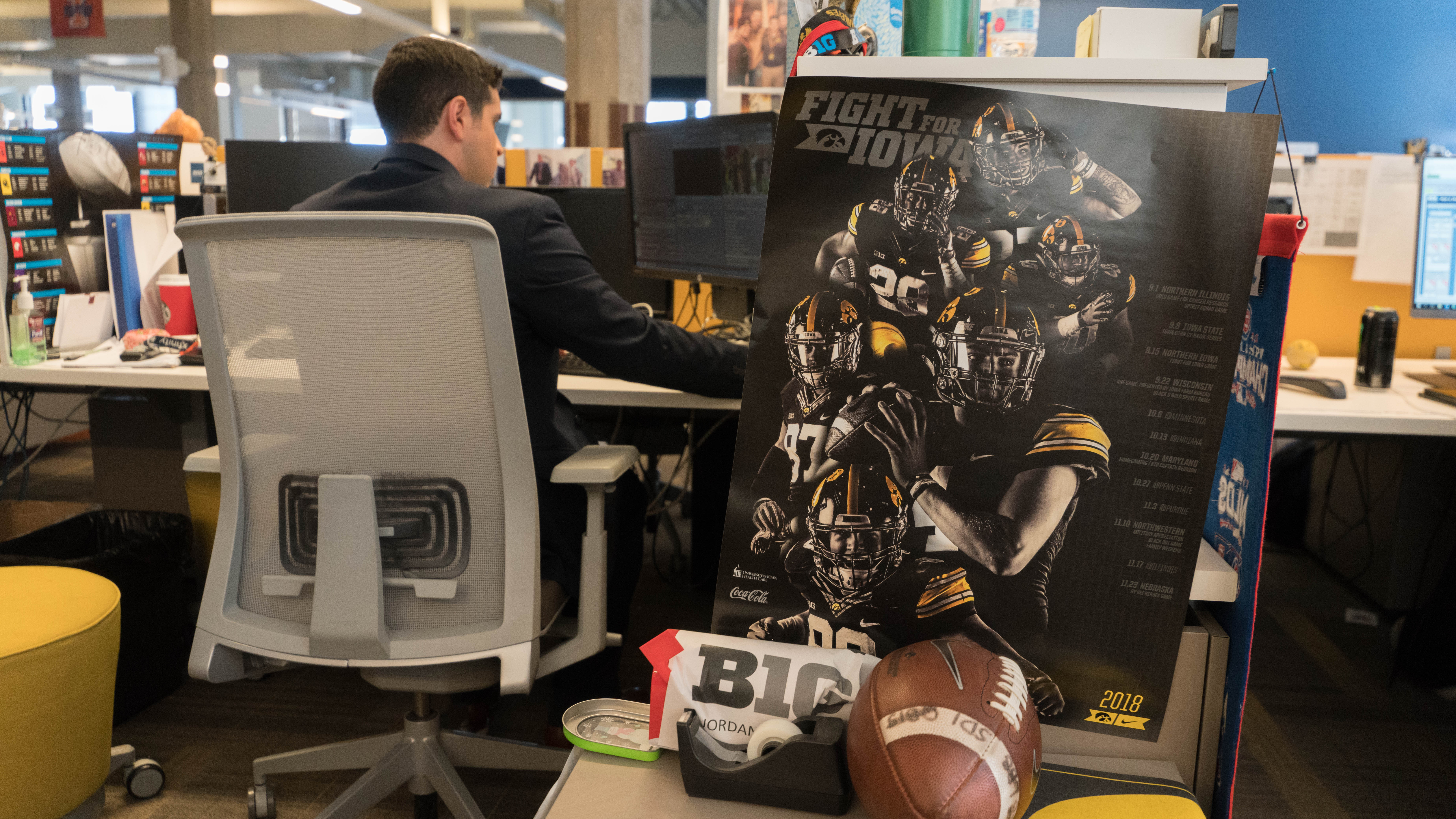 University of Iowa graduate Jordan Loperena at his desk, which features a university of iowa football poster