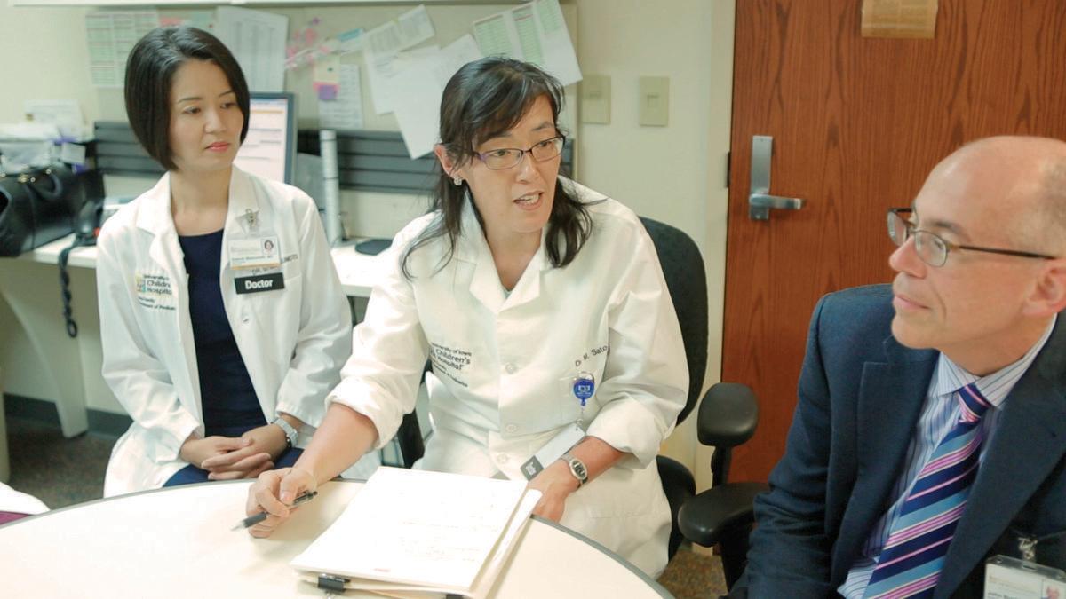 Neuro-oncologist Mariko Sato discusses Brady Jorgensen's case with team members in the Pediatric Brain Tumor Clinic.