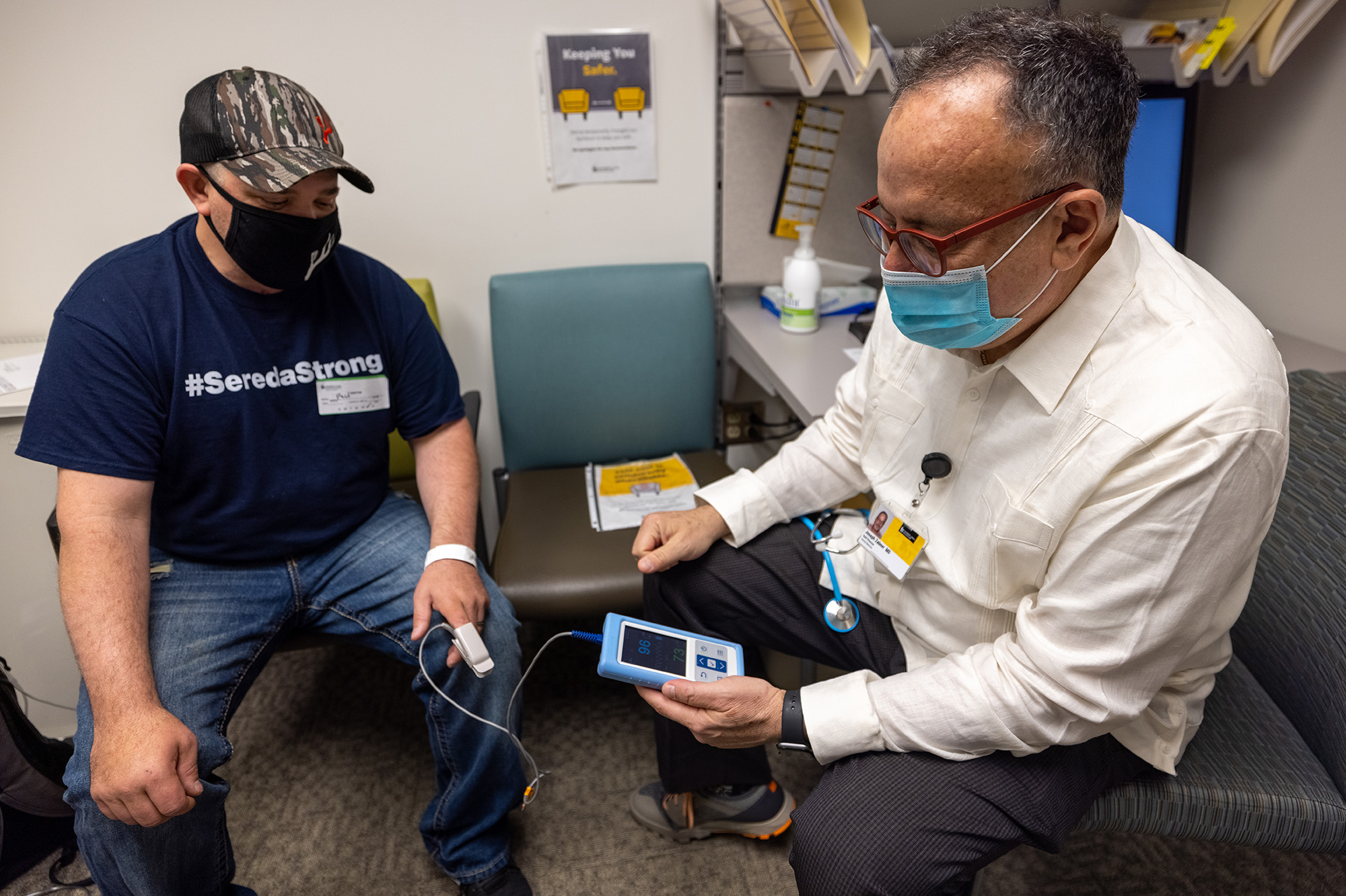 a patient and a medical professional in an exam room; the medical professional is monitoring the patient's vitals such as oxygen levels using a handheld device