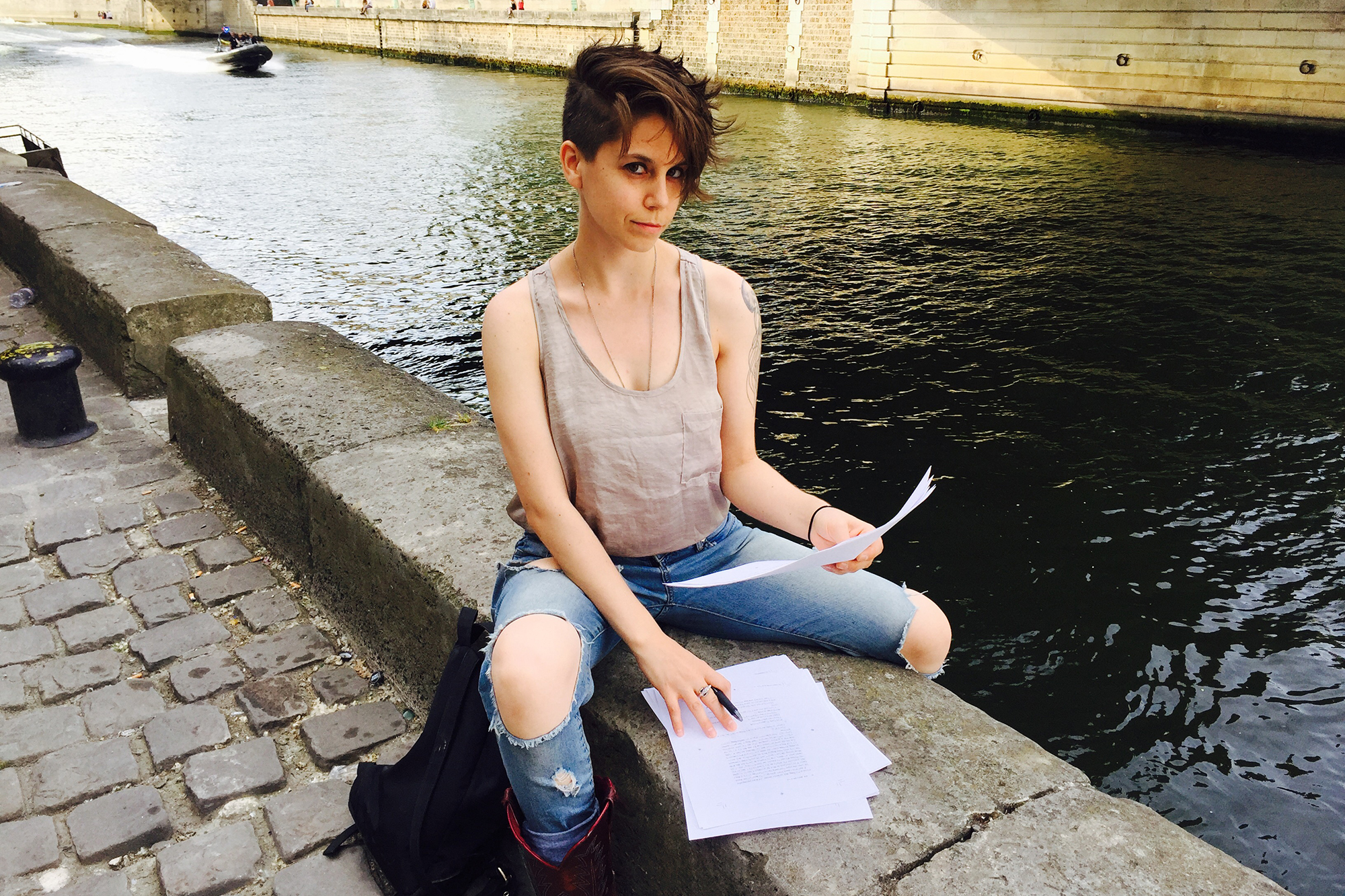 University of Iowa alumna Jen Silverman sit on the banks of a river with papers in hand and in front of her
