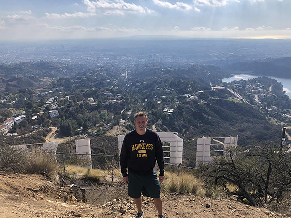 University of Iowa alumnus Doug Johnson standing behind the large Hollywood sign