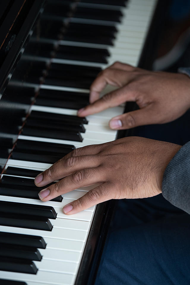 close-up of student's hands on piano keys