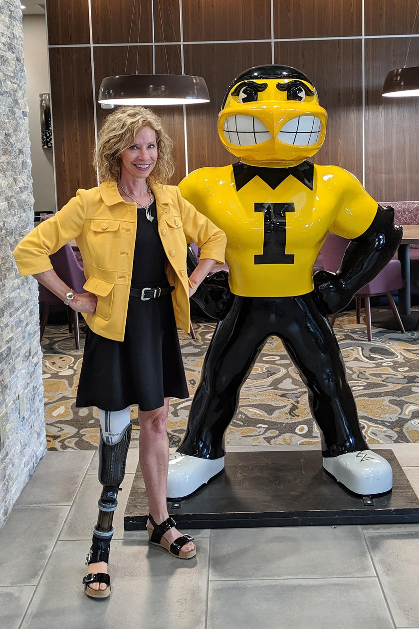 University of Iowa alumna Deborah Smith stands near a Herky statue