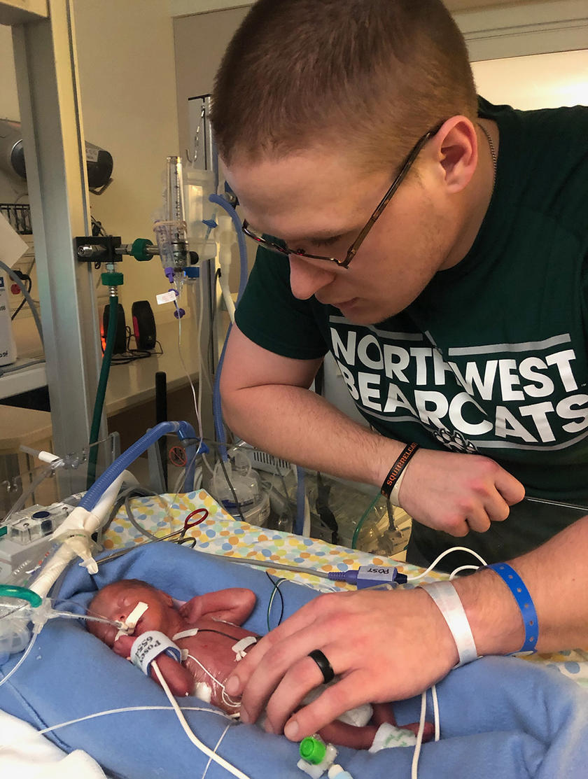 Dylan Leech stands beside the bed of his son Warren who weighed just 1 pound 14 ounces at birth