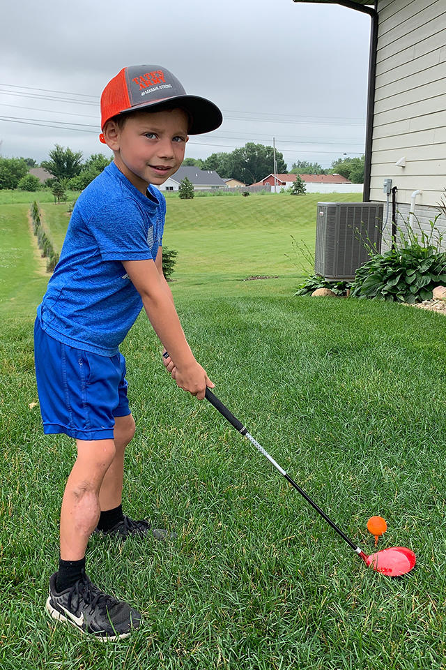 Tate Manahl works on his golf game at his home
