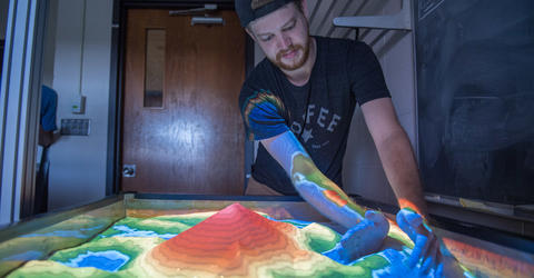 Student in the Department of Physics and Astronomy works on an augmented-reality sandbox where users can design their own universe and then watch how gravity affects an object as it travels through the imagined environment.