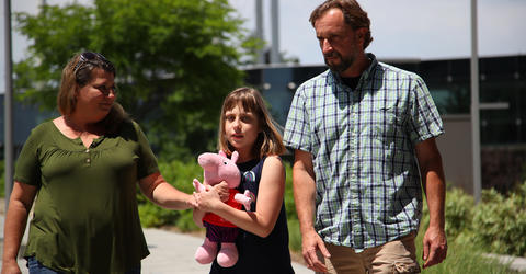 a young girl holding a stuffed animal walking with her parents