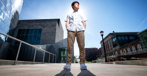 University of Iowa Master of Fine Arts student Hao Zhou standing on campus on a sunny day, looking to his left