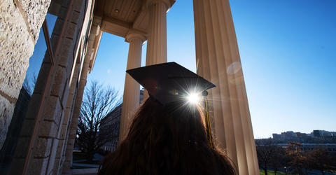 Graduate looking up toward Old Capital pillars