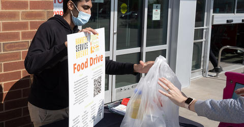 Prateek Raikwar, a third-year neuroscience and music major from Iowa City, works at a food drive for Hawkeye Service Breaks