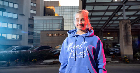 University of Iowa student Maggie McQuillen stands near an emergency entrance. she is illuminated by emergency lights