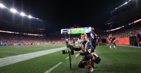 university of iowa alumnus cole cooper holding a camera on the sidelines of a denver broncos game
