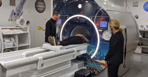 two people standing near an MRI machine with space visuals applied to it; a third person is the opening of the machine