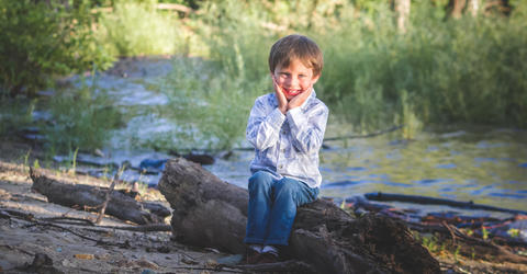 Tate Manahl sits outdoors; when he was 3, he was injured in a lawn mowing incident, and university of iowa health care professionals performed numerous procedures to save his life and his legs