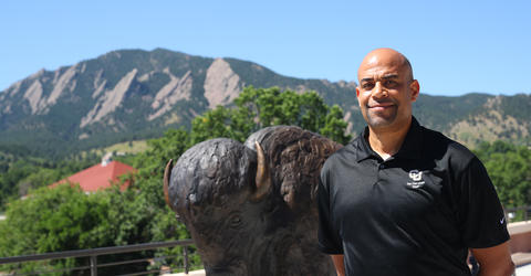 university of iowa alumnus tony price standing on the university of colorado boulder campus with the mountains in the background
