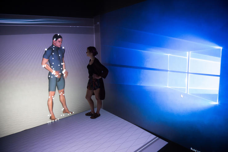 A University of Iowa student stands in front of a virtual human simulator