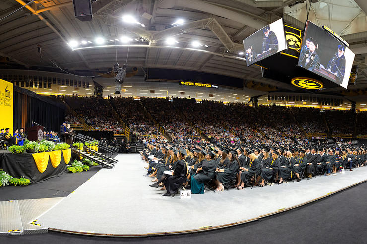 University of Iowa graduates gathered together in an arena for commencement ceremonies