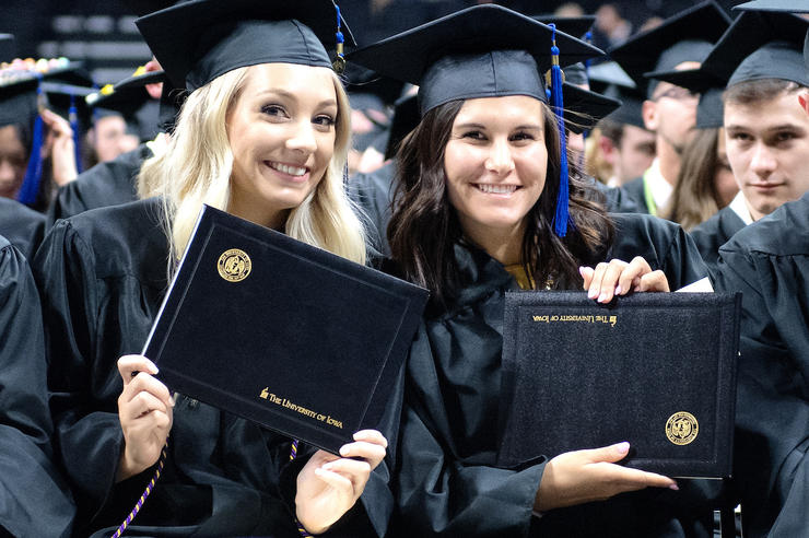 graduates holding their diplomas, which have the words The University of Iowa in one corner