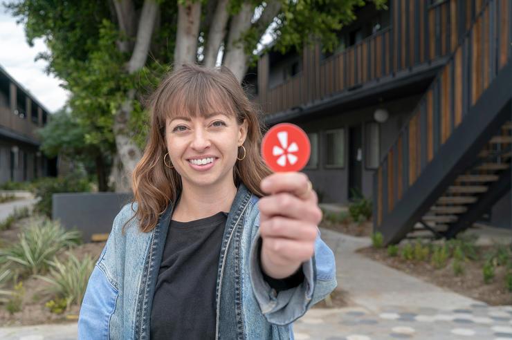 university of iowa alumna megan ranegar holds up a yelp icon