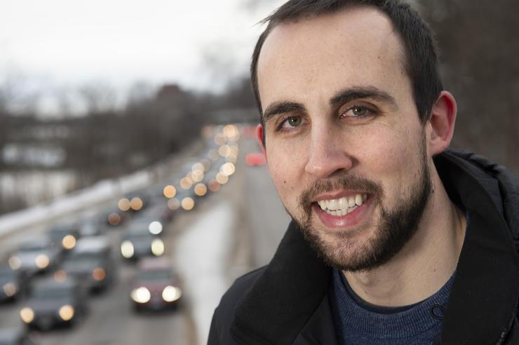 University of Iowa doctoral student Michael Redmond posing near a busy street