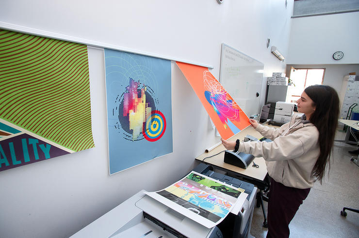 a person hangs artwork in a university of iowa graphic design class