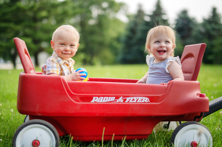 two young children smiling while sitting in a red wagon