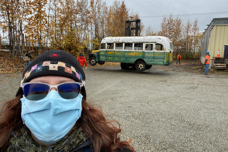 """University of Iowa alumna Angela Linn with the """"Into the Wild"""" bus in the background"""